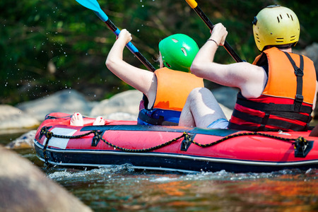 in unison: Group young person are rafting on the river, extreme and fun sport at tourist attraction Stock Photo