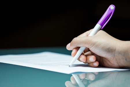 Close-up businessperson signing agreement contract on desk