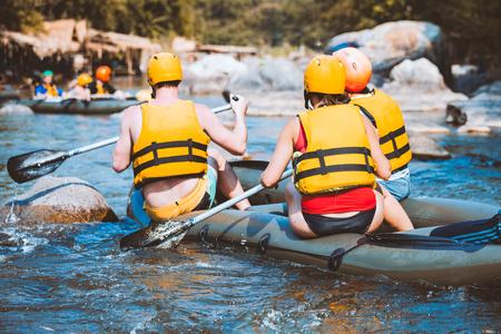 Junge Männer und Frauen raften auf dem Fluss, extremer und lustiger Sport bei Touristenattraktion