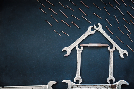 Metal wrenches in the shape of a house with rainy storm on blackboard. Made for text or brand.