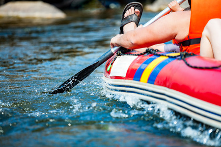 paddles: Focus some part of young person are rafting in river.