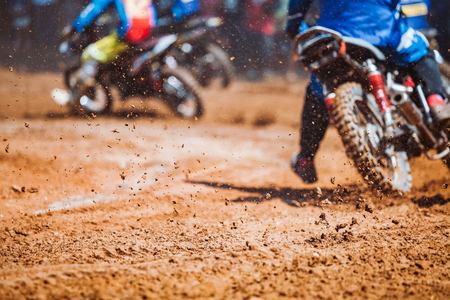 Details of flying debris during an acceleration with mountain bikes race in dirt track in sunshine day time in blurry background. Concept of focus between an accelerate in action sport Stock Photo - 89598637