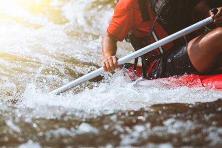 Jugendlicher, der auf dem Fluss, dem Extrem und dem Spaßsport an der Touristenattraktion flößt