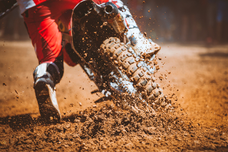 Details of flying debris during an acceleration with mountain bikes race in dirt track in sunshine day time in blurry background. Concept of focus between an accelerate in action sport Stock Photo
