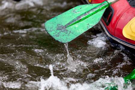 Close-up some part of paddle while young person rafting on the river, extreme and fun sport at tourist attraction natural park