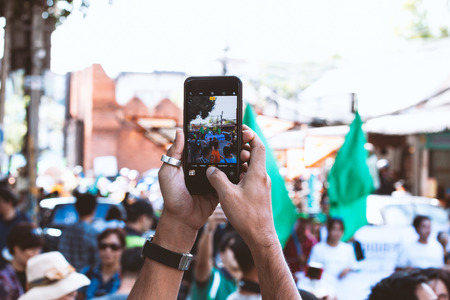 Young man taking photo of events using mobile phone