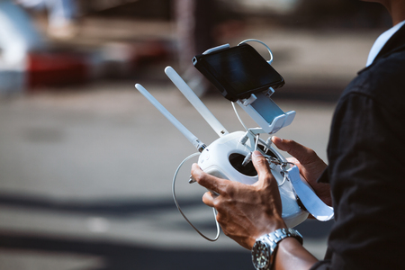 Close-up of man hand navigating a flying drone with remote control