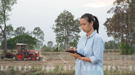 Futuristic asian female farmer using portable tablet computer in farmland. Modern hologram farming concept, advanced technology in agriculture. 免版税图像