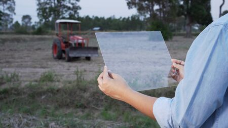 Asian female farmer using portable plate computer to inspect the agricultural engine in farmland. Modern hologram farming concept, advanced technology in agriculture.