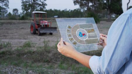 Asian female farmer using portable tablet computer to inspect the agricultural engine in farmland. Modern hologram farming concept, advanced technology in agriculture.