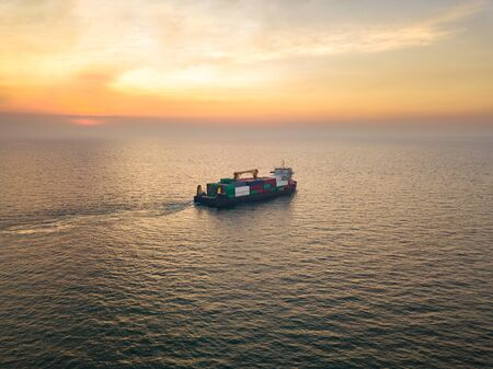 Aerial view from drone, a cargo vessel with peaceful sea in beautiful scenic sky. Professional business logistics and transportation of cargo ship.