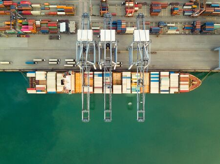 Aerial drone view above dockyard. Cargo vessel is loading containers. Professional business logistics and transportation of cargo ship.
