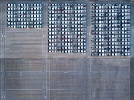 Aerial drone view above new cars at parking lot waiting for export to customer. Professional business logistics and transportation of cargo. 免版税图像