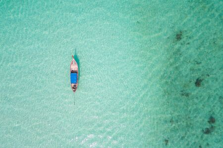 Aerial view or top view of long-tailed boat is float on the emerald sea at Koh Lipe island in Satun, Thailand. - Image