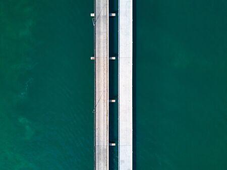 Aerial top view of a long highway bridge above a ocean. Vertical  highway