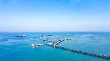 Aerial view from drone, Oil pipes to oil tanker ships at pier off the coast in beautiful peaceful environment. Professional business logistics and transportation of energy fuels.