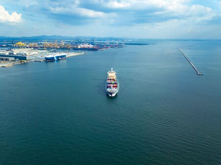 Aerial view from drone, Cargo vessel sail to the sea at port cargo ship. Professional business logistics and transportation of cargo ship. 免版税图像