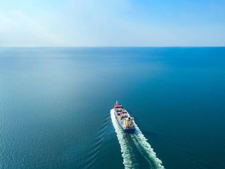 Aerial view from drone, Cargo vessel sail to the sea with peaceful wave in beautiful scenic sky. Professional business logistics and transportation of cargo ship.