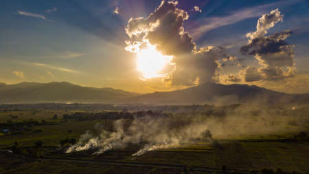 Aerial view. The morning sunrises with dry grass is burning on the field. Burning old chaff on the farmland.