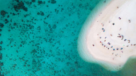 Aerial view or top view of beautiful curve beach with traveller relaxing with the emerald sea at Koh Lipe island in Satun, Thailand. Space for text. - Image