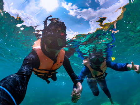 Happiness couple taking selfie under tropical sea by water camera while excursion - Image