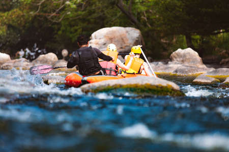 Close-up of young people rafting on the river turbulent flow. Extreme and enjoyment sport. 免版税图像