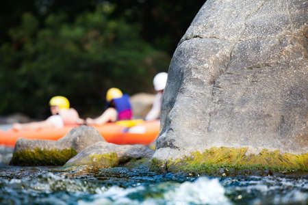 Close-up of reef with group of young people are rafting on the river, at tourist attraction.