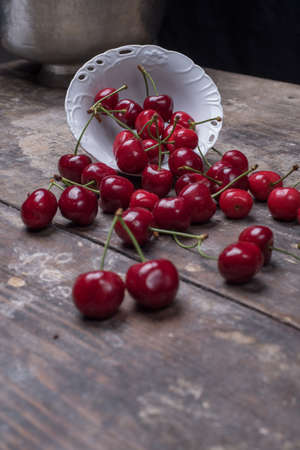 falling out: cherries on table falling out of bowl