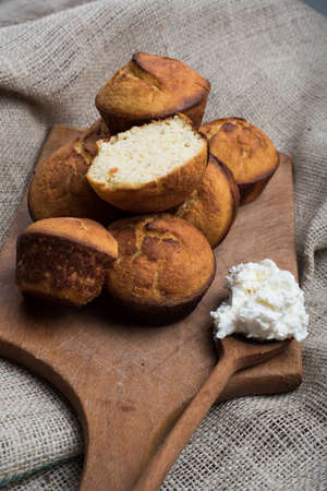 chees: muffines on wooden board and domestic chees on spoon