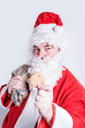 happines: santa holding cookie in  hand Stock Photo