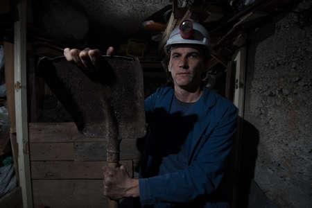 the miner: miner sitting and holding shovel Stock Photo