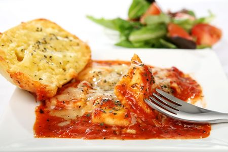 A dish of ravioli topped with mozzarella cheese served with a green salad and crusty garlic cheese bread photo