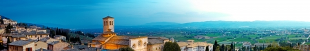 basillica: A very wide panoramic view of the beautiful Umbrian town of Assisi in Italy with residences on the rolling hillside and a bright blue sky at sunrise