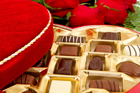 A box of assorted chocolate candies with red roses around them photo