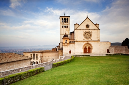 st  francis: The beautiful Basilica of St. Francis of Assisi located in the town of Assisi, Italy. Photo contains a Tuscan hillside view in the background and a bright blue sky with pretty cloud formations.