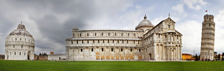 intentional: A wide panoramic photograph of Piazza dei Miracoli containing the Leaning Tower of Pisa, the Cathedral and Duomo. Photograph was taken with a very long exposure to create intentional motion blur on the tourists. Stock Photo