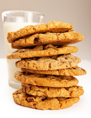 chocolate chip cookies: A stack of golden chocolate chip cookies with a glass of milk Stock Photo