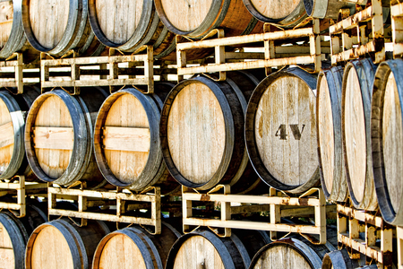 fermenting: A large rusty rack of old oak wood barrels containing wine that is fermenting in at California winery