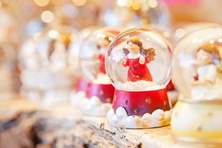 A row of Christmas snow globes on an outdoor table with focus on an angel photo