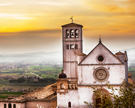 Scenic view of the belltower of the St Francis of Assisi church at sunrise with the green rolling hills of the Umbrian valley in the background Stock Photo