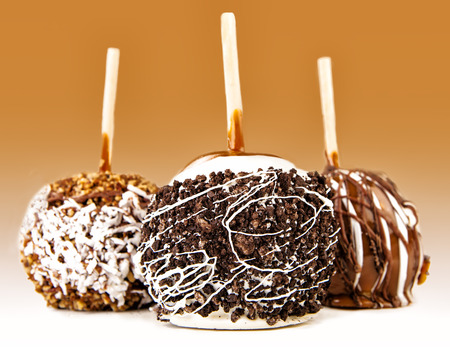 Three delicious gourmet candy apples on sticks topped with caramel, chocolate, nuts, coconut and fudge