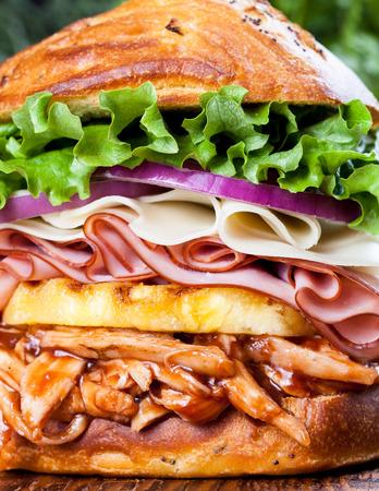 sandwich de pollo: Un sándwich de pollo hawaiano alto con pollo a la barbacoa, piña, jamón, queso provolone, cebolla y lechuga verde en un bollo cebolla