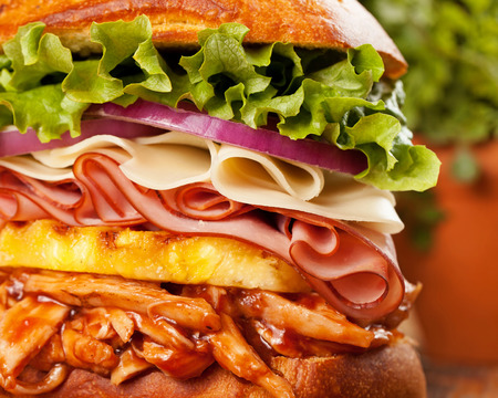 A tall Hawaiian chicken sandwich with barbequed chicken, pineapple, ham, provolone cheese, red onion and green lettuce on an onion bun Stock Photo