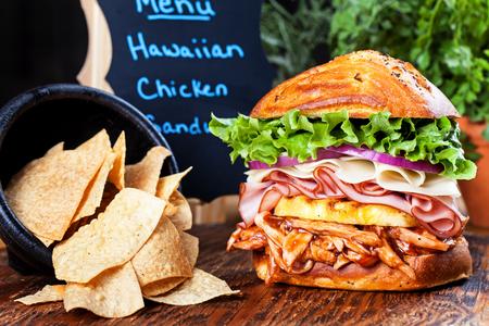 sandwich de pollo: Un sándwich de pollo a la barbacoa hawaiana alto con chips de tortilla en el lado