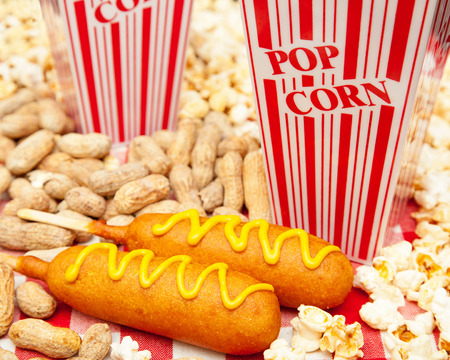 wiener dog: Classic American baseball park snack including two delicious corn dogs with piles of popcorn and peanuts