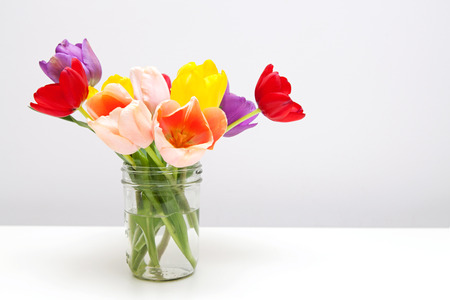 A bouquet of colorful tulip flowers in a jar sitting on a white table with room for text