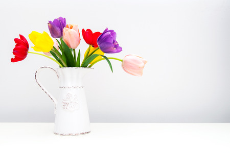 Bouquet of beautiful spring tulip flowers in an old vintage milk pitcher sitting on a white table with room for text photo