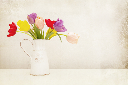 Bunch of colorful tulip flowers in an old milk pitcher. Antique textured filter effect applied. photo