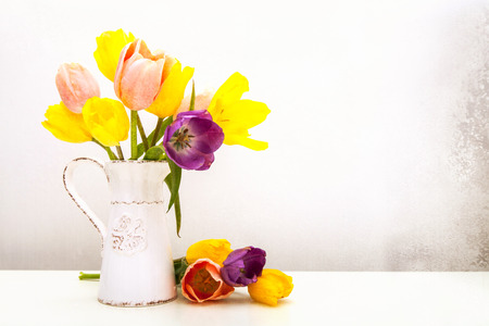 Beautiful bunch of tulips in an old milk pitcher with loose flowers resting on a white table. Aged textured photo filter effect applied. photo