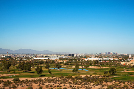 phoenix arizona: Beautiful overhead view of the city of Phoenix, Arizona, USA with a golf course in the foreground and downtown buildings in the background. Image taken from the Papago Mountains.